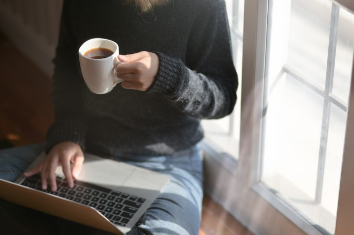 Woman Using Laptop While Holding A Cup of Coffee.jpg